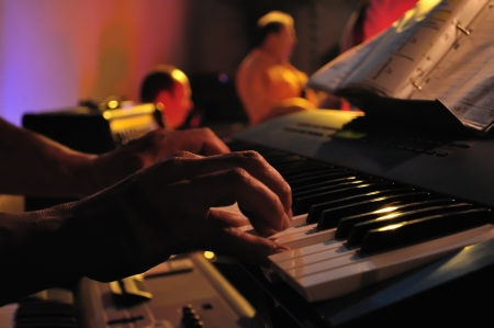A closeup of a pair of hands playing a piano in concert  photo
