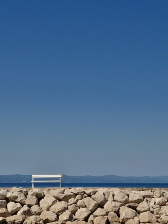 White bench in port with stones and blue sky Stock Photo