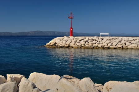 Red lighthouse in port with stones and white bench photo