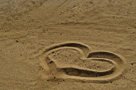Love symbol drawn in the sand photo