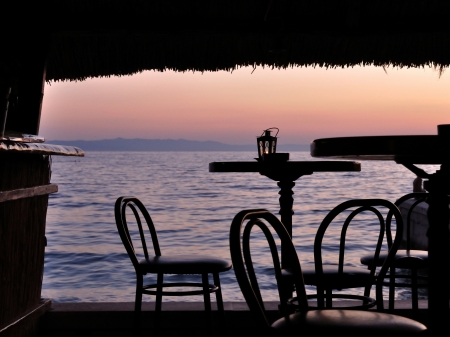 Silhouette of bar chairs and tables in the tropical bar with sea in background at sunset