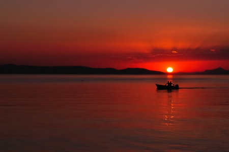 Silhouette of two people in the boat on the sea at sunset