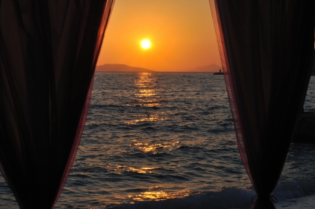 Sunset at sea across the curtain