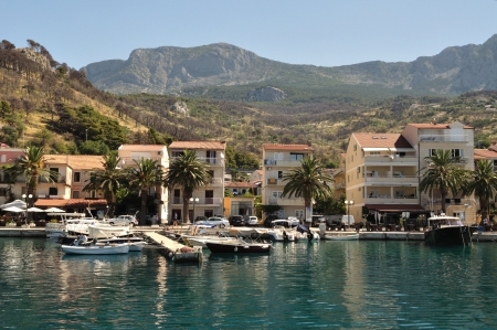 Port of Podgora in Croatia with apartments, boats and with mountain Biokovo in background