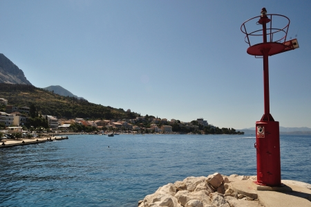 Red lighthouse in port in Podgora