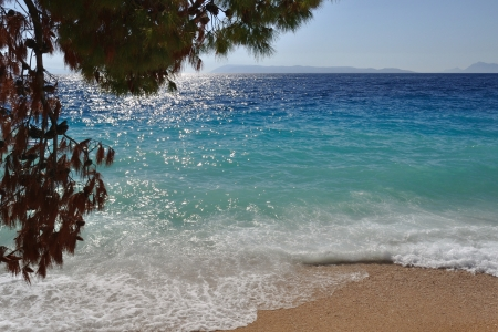 Waves on beautiful beach with sand and in Podgora  Part of tree in left top side of the frame