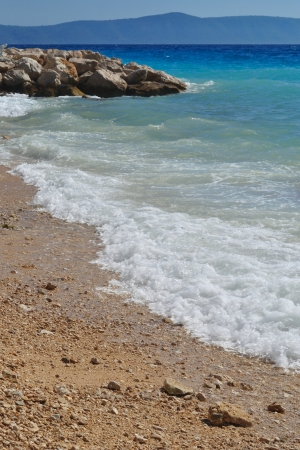 Waves on beautiful beach with sand and stones in Podgora Stock Photo