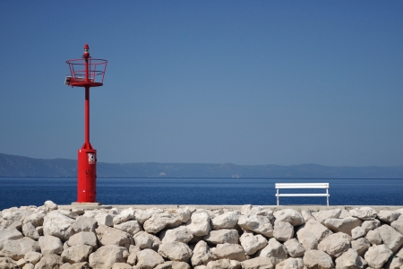 Red lighthouse in port with stones and white bench