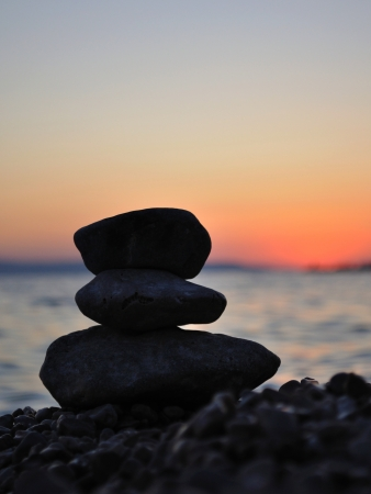 Silhouette of three zen stones on the beach at sunset