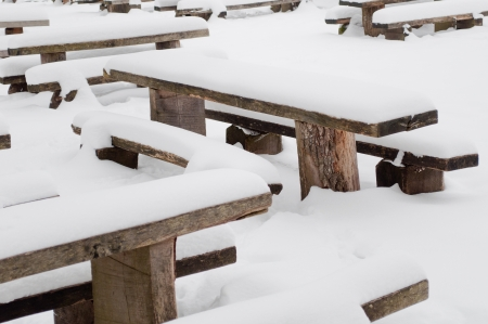 Winter scene with some park bench and lot of snow photo