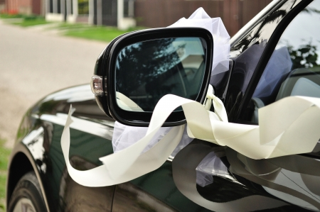 Mirror of black wedding car decorated with ribbon