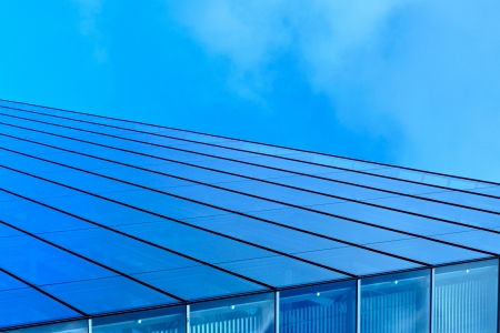 Abstract view of modern blue glass business center on a clear sky background photo