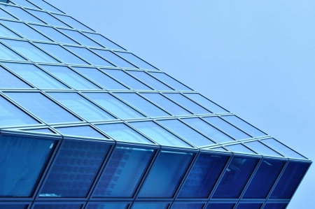 Abstract view of modern blue glass business center on a clear sky background Stock Photo