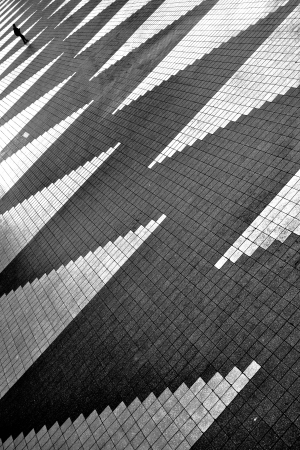 Lonely man is going away on empty square with zigzag pattern  Black and white photo