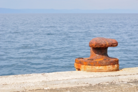 Old, rusty mooring bollard on port of Podgora, Croatia photo