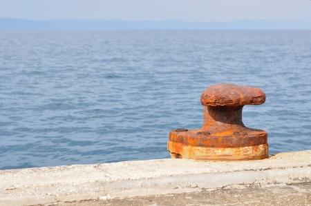 Old, rusty mooring bollard on port of Podgora, Croatia