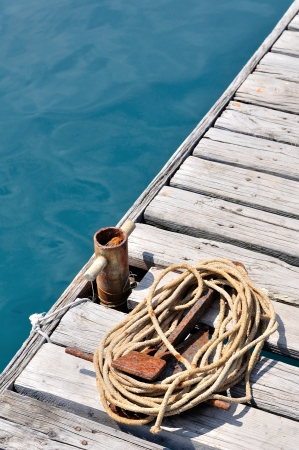 Coiled marine rope and small, old rusted mooring bollard on wooden pier  Podgora, Croatia Stock Photo
