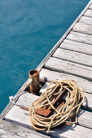 bollard: Coiled marine rope and small, old rusted mooring bollard on wooden pier  Podgora, Croatia Stock Photo