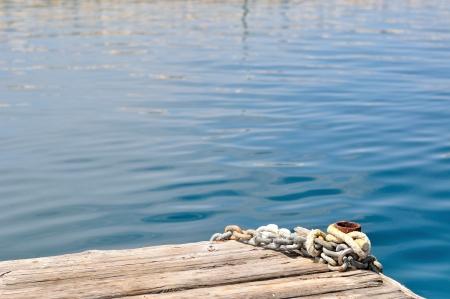 Metal ship chains and mooring bollard on wooden pier  Podgora, Croatia photo