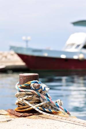 coiled rope: Marine rope on mooring bollard in port of Podgora, Croatia  Blurred ship on background