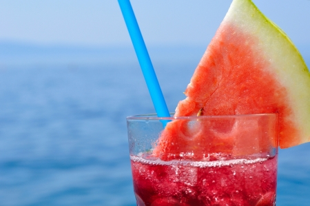 Fresh tropical fruit cocktail with water melon slice on a beach  Blurred sea on background  Space on left side