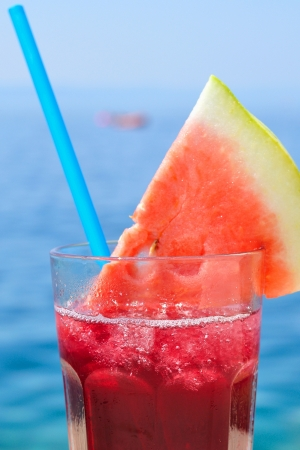 Fresh tropical fruit cocktail with water melon slice on a beach  Blurred sea on background  Vertical image
