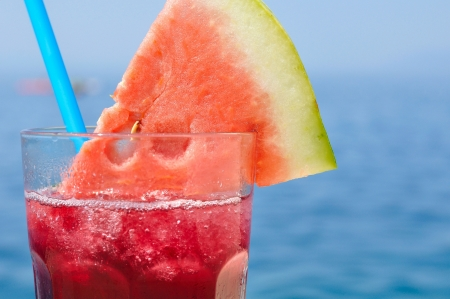 Fresh tropical fruit cocktail with water melon slice on a beach  Blurred sea on background  Space on right side  Stock Photo