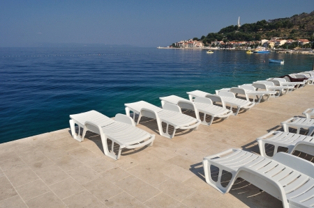 Adriatic sea at Podgora in Croatia with monument Seagull s wings and mountain Biokovo in background  Empty sunbeds in front  Stock Photo