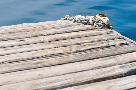 coiled rope: Metal ship chains and mooring bollard on wooden pier  Podgora, Croatia Stock Photo