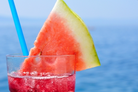 Fresh tropical fruit cocktail with water melon slice on a beach  Blurred sea on background  Space on right side  photo