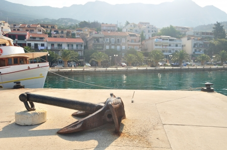 Port of Podgora in Croatia with apartments, ship and with mountain Biokovo in background  Old rusty anchor in front