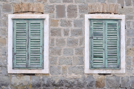 Two old windows with blue closed shutters on an old house  Vintage background, texture