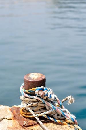 Marine rope on mooring bollard in port of Podgora, Croatia  Vertical photo  photo