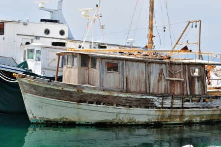 Old abandoned wooden fishing ship on port photo