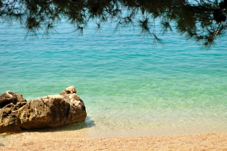 Beautiful beach with big stone framed by tree  Tucepi, Croatia Stock Photo