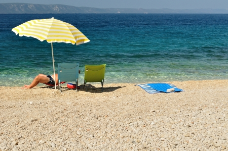 Man resting under yellow umbrella and enjoying a quiet summer day on the adriatic beach of Croatia photo