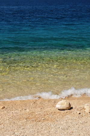 Beautiful beach with wave and big stone in right bottom side of photo  Podgora, Croatia photo