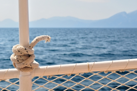 Marine knot detail on steel boat banister with blurred sea in background
