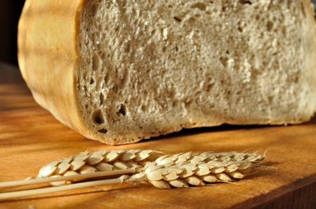 Fresh bread with ear of wheat on kitchen table Stock Photo