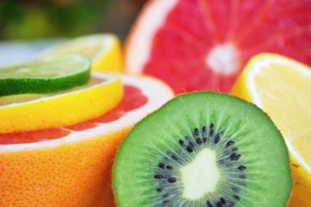 Fresh colorful tropical fruits and slices - kiwi, lemon, lime, red grapefruit