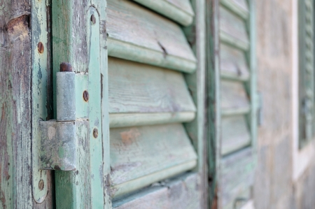 Detail of closed green old wooden shutter in perspective photo