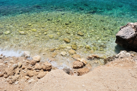 Beautiful beach with big stones and crystal clear adriatic sea in Podgora, Croatia