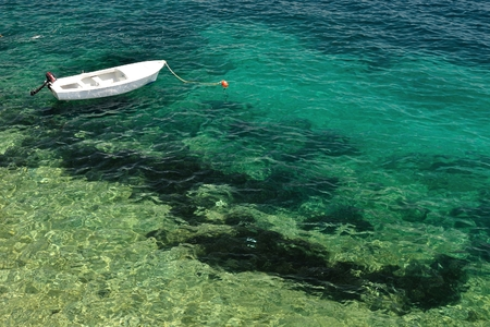 Small lonely fishing boat floating alone on adriatic sea in beach of Korcula, Croatia