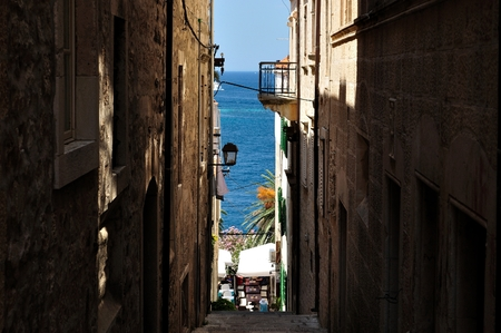 Narrow street in old medieval town Korcula by sunny day   Dalmatia, Croatia, Europe photo
