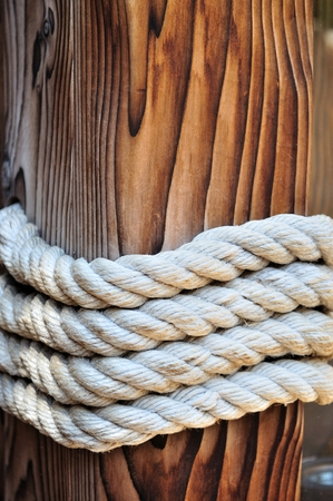 Thick rope around a wooden mooring bollard keeping a boat docked  Croatia photo