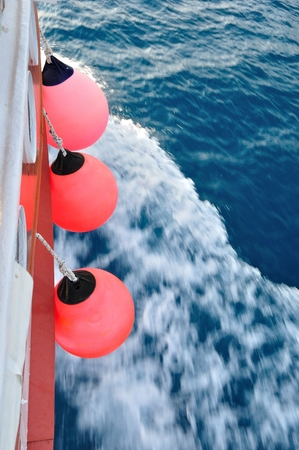 Red buoy on body of moving ship  Waving adriatic sea in right part of image  Vertical image