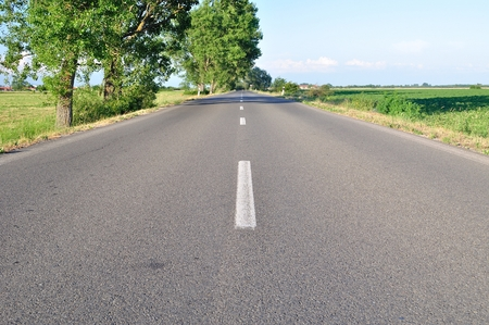Asphalt road with green trees and blue sky in summer day  Horizontal image Stock Photo