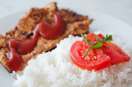 Chicken steak in a dish served with rice and vegetable