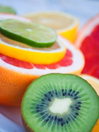 Fresh colorful tropical fruits and slices - lemon, kiwi, lime, red grapefruit. Vertical image