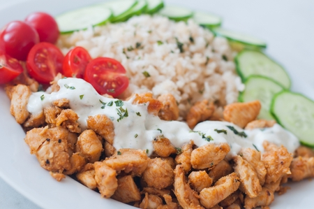 Gyros chicken on a plate with rice, tzatziki dressing and vegetables - tomato, cucumber